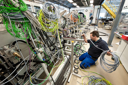 A technician handles the many wires and hoses: at Ampulse's pilot production line being installed in NREL's PDIL.  Credit: Dennis Schroeder