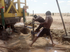 Technicians install a submersible pump in a borehole prior to test pumping.: PHOTOGRAPH © UNESCO/Nairobi Office