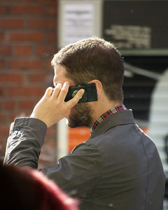 Man speaking on mobile phone: A mobile phone can contain 500 to 1,000 components. Many of these contain toxic heavy metals such as lead, mercury, cadmium and beryllium, and hazardous chemicals, such as brominated flame retardants (BFR). Photograph courtesy of Wikipedia.