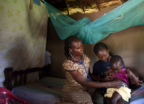 In a rural village outside of Kisumu, Kenya, a healthcare worker examines a child for possible symptoms of malaria.