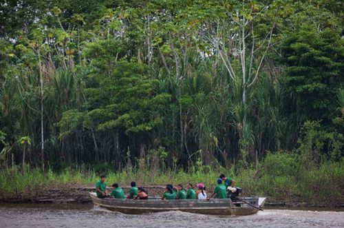 Healthcare workers on the way to visit a community deep in the Peruvian Amazon.: Healthcare workers on the way to visit a community deep in the Peruvian Amazon. The journey from Iquitos to the village takes two days by canoe.