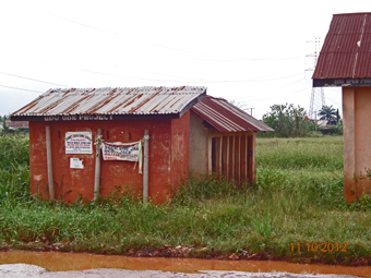 School latrine overtaken by weeds and flood water.